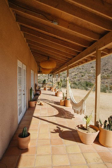 a long terra cotta-tiled, shaded porch with a hammock runs the length of the house