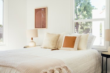 Bedroom with neutral bedding, retro lamps on each side and contemporary wall art