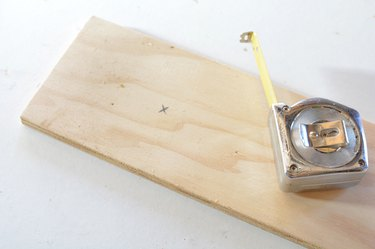 a tape measure sits on top of the base panel with an x penciled on it