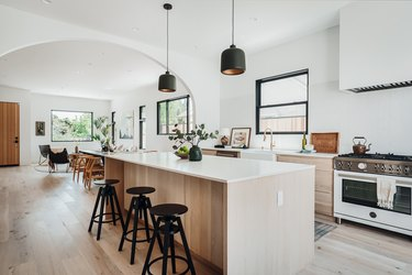 White counter and wood base kitchen island with black stools and black pendant lights above.