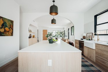 Large white and wood kitchen island with black pendant lights, farmhouse sink, and brass faucet, plaid floor rug. Black window frames.