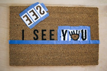 a brown doormat with a horizontal tape guideline and templates for one word taped in place