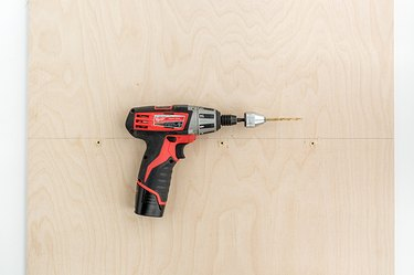 a power drill lies on a sheet of plywood