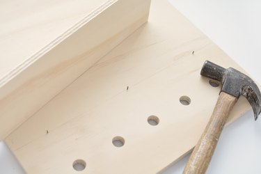 a hammer lies on a sheet of plywood with holes drilled in it and nails sticking through from the other side