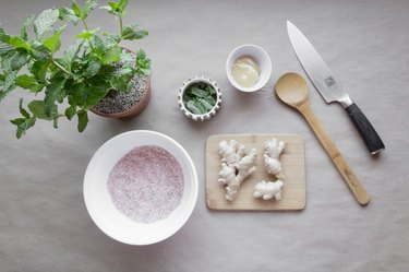 ginger root on a cutting board surrounded by bowls of mint, salt, and glycerine