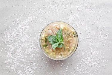 a jar of body scrub with a fresh mint leaf on top
