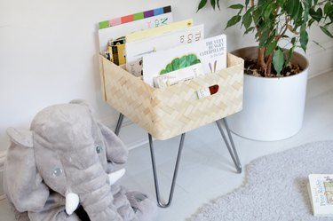 Light tan book bin with metal legs and picture books in a white room with grey rug next to elephant stuffed animal and medium-sized plant