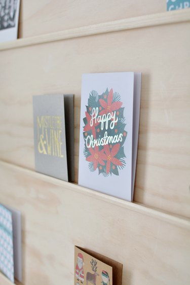 close-up on holiday cards sitting on shelves made from thin strips of moulding glued to a plywood sheet