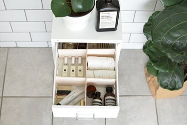 an open bathroom vanity drawer with dividers and cosmetics
