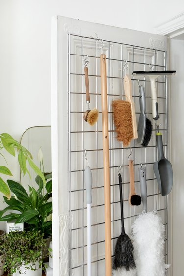 cleaning supplies such as brushes and a squeegee hang from metal hooks attached to a metal grid on a door
