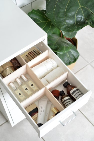 Makeup Organizer Ideas on an open bathroom vanity drawer with dividers and cosmetics