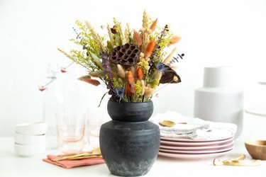 dried flowers in earthy fall colors, including lotus pods and bunny tails dyed burnt orange, in a black earthenware vase surrounded by dinnerware