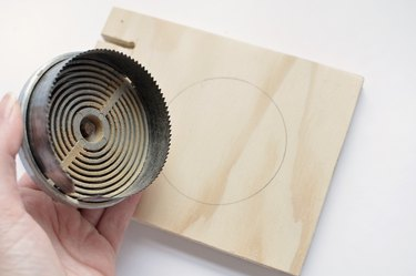 a hole saw next to a square of plywood with a circle marked on it