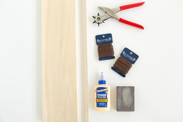 Wood board, dowel, packets of leather, wood glue, sanding block, and leather hole punch