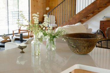 A white counter with vases of flowers, a wood bowl, and a small pewter dish. A wood staircase in the distance.