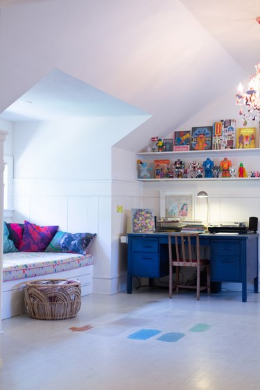Homeschool Organization with Blue kids desk, open white shelves with toys, window seat.