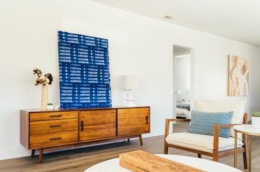 Wood sideboard with a contemporary art piece, dry flowers in vase, a white lamp. Wood armchair with white cushions and blue pillow.