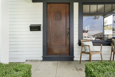 A wooden front door with black trim and a wooden chair on the front porch