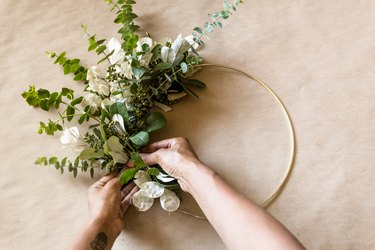 attaching greenery to a brass hoop to make a diy wreath