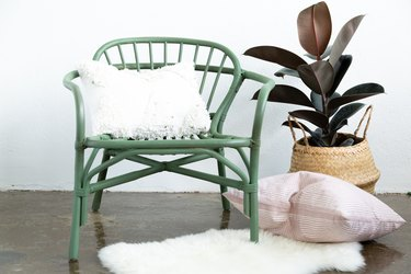 Green rattan chair with pillows, potted plant in basket, and sheep rug