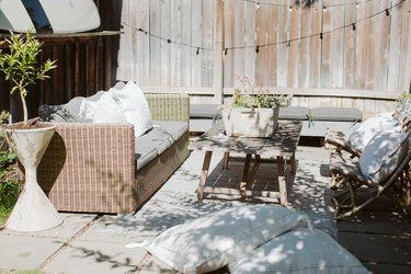 An outdoor patio with a wicker couch, two chairs, and a patio table