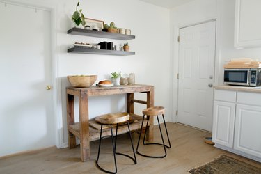 White cabinets and wood floor kitchen, wood stools at a wood side table, black shelves with dish ware.