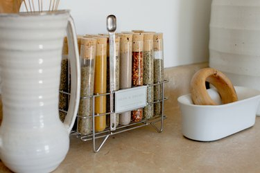 'Dean & DeLuca' spice vials and white dish ware on a neutral kitchen counter