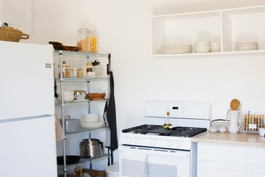 Kitchen with metal racks of dish ware and containers of dry goods, stove, white cabinets and beige counters, white dishes