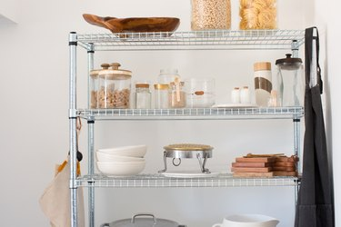 Metal shelf racks with clear containers of dry goods, white dish ware, wood cutting boards, and a gray cast iron pot.