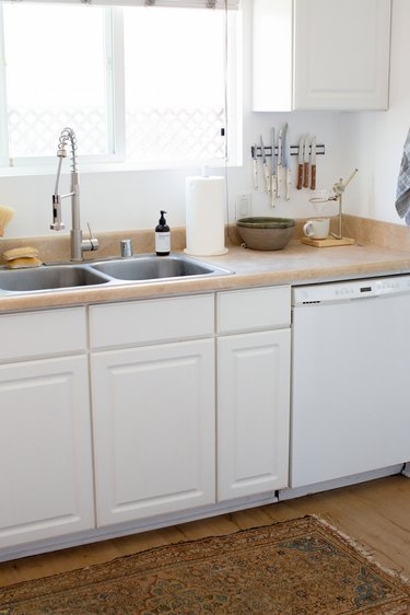 white kitchen with colorful rug underneath