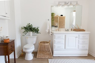 Shabby Chic Bathroom Storage in Bathroom with white vanity, mirror, basket, end table, toilet, rug, plant.