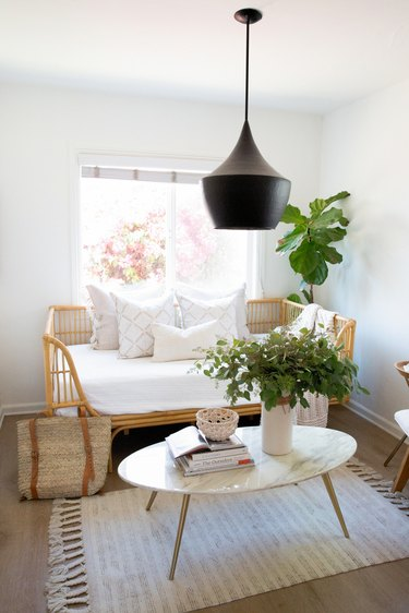 Black pendant light over an oval white coffee table with a vase of flowers and books, rattan bench with white pillows