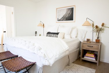 Minimalist bedroom with white bedding, wood nightstand with rattan sconce shades, leather latticed stools.