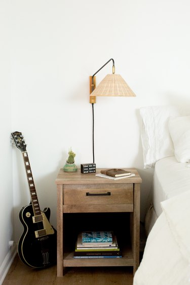 Rattan shade sconce over a wood night stand with books, and a black electric guitar