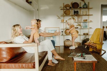 Parents playing with their young children in boho living room