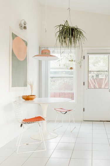 White boho kitchen with tulip table and hanging plants