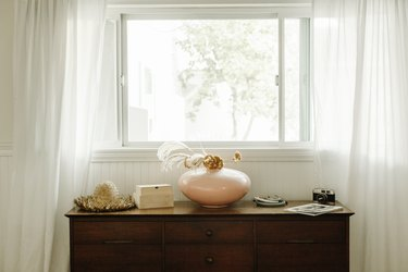 Open window with white flowing curtains, a dark wood credenza below with neutral decor
