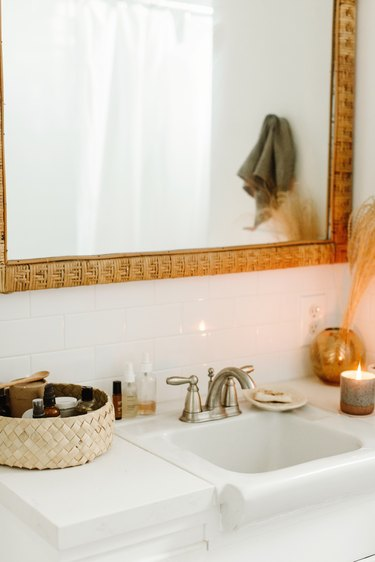 small boho bathroom with large mirror above sink