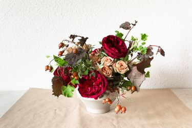 a diy floral centerpiece made of caramel roses and red flowers  including ranunculus and zinnias
