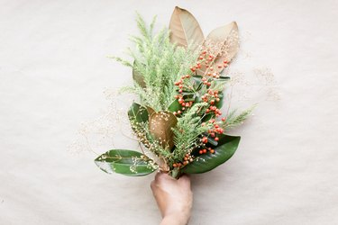 Hand holding winter-themed foliage bouquet