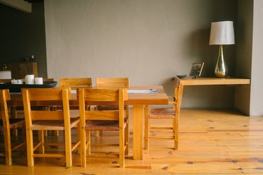 Mid-Century wood dining table set on wood flooring, a corner side table with a lamp