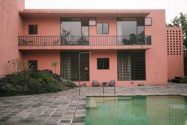 Slate patio with swimming pool and pink Midcentury building with large windows and balcony Home Exterior Ideas