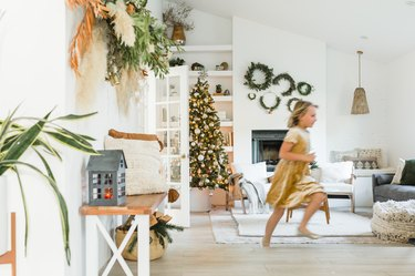 Young girl running through large living room with boho Christmas decor