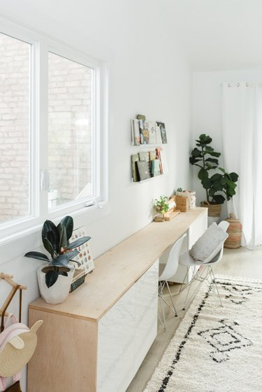 Long white and wood dresser in boho room with fiddle fig plant