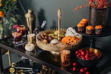 Gold cake stand with Halloween cookies and autumnal flowers and pumpkin decor