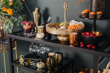 Bar cart with gold cocktail set, cake stand, and autumnal decor