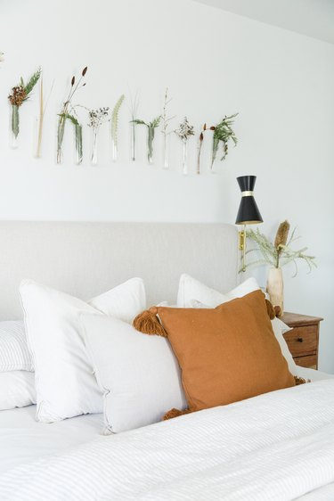 White boho bedroom with glass hanging vases above bed