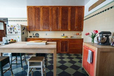 Kitchen with wood cabinets and dining table, stools, walls with beige tiles and triangle accent tiles, a portable cabinet with pink doors.