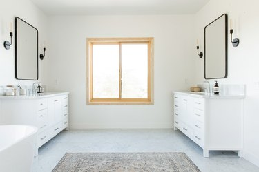 A bathroom with a light wood frame window. Double white vanities, black incandescent light sconces, black frame mirrors are on either side. There is a freestanding tub and a neutral patterned rug.
