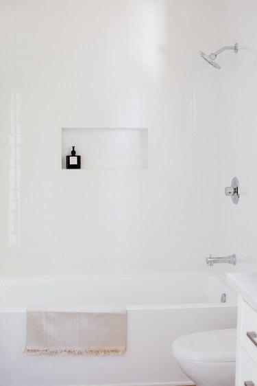 Bathroom with white walls, white tub, white toilet.